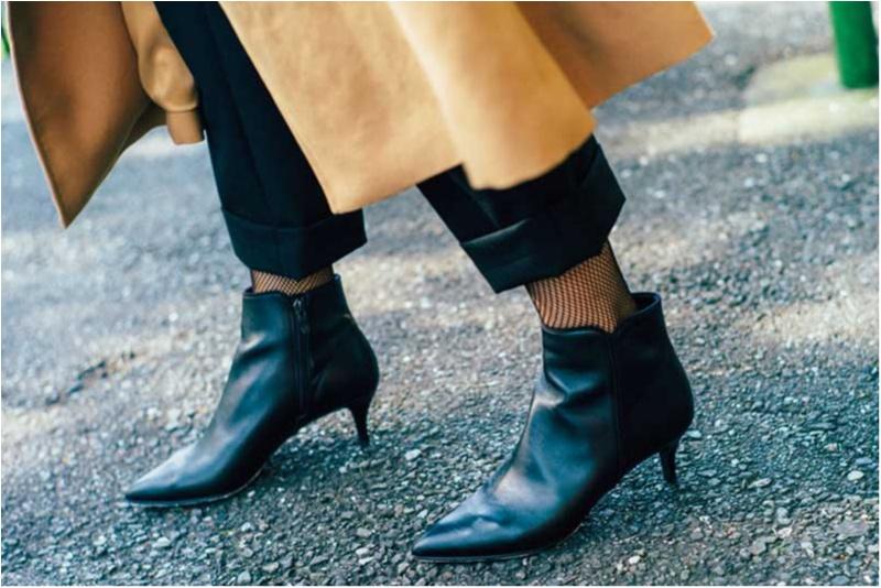 トレンチコートの裾から黒いパンツと網タイツ