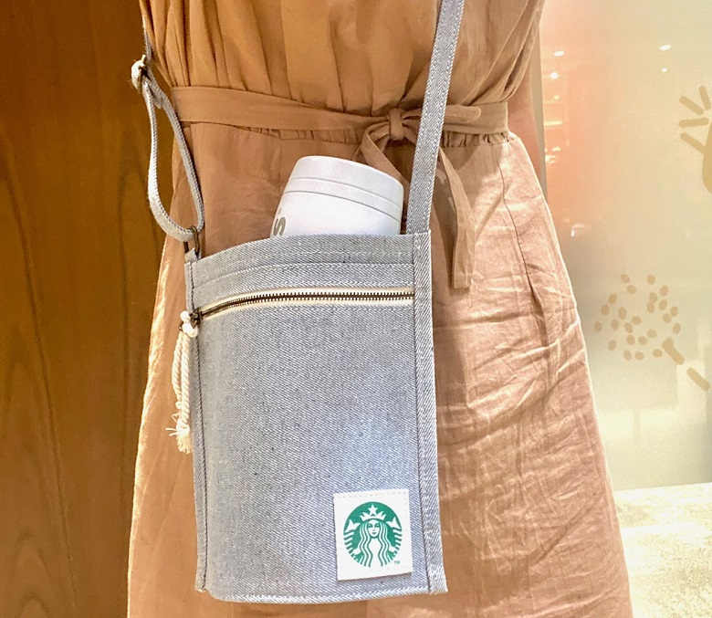 「スターバックス アップサイクルコットン ボトルサコッシュ デニムブルー」を女性が使っているイメージ
