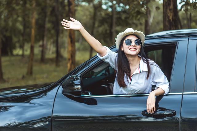 車の助手席から外に向かって手を振る女性