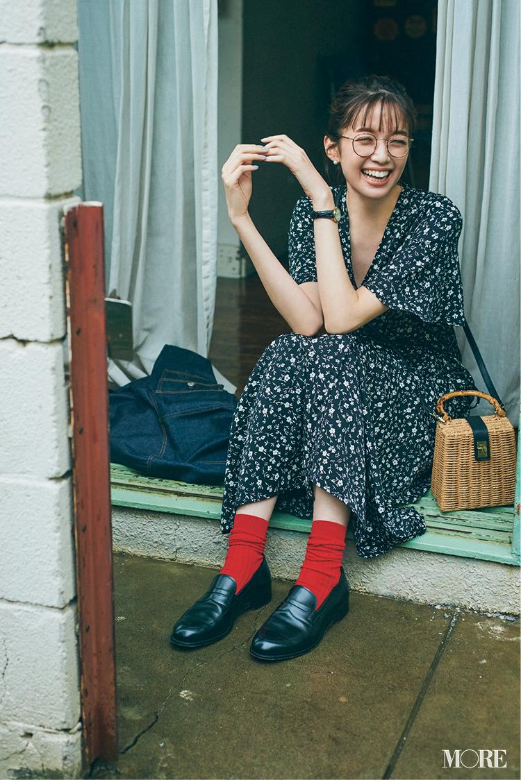 黒ベースの花柄ワンピースにメガネをかけてぺたんこ靴を履いた佐藤栞里