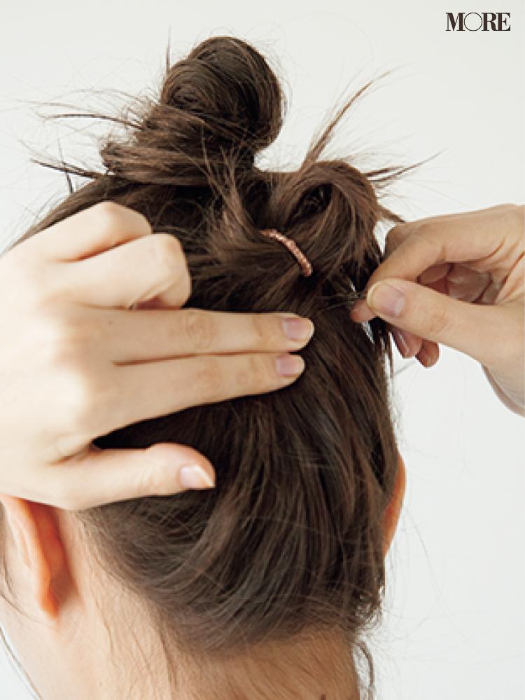 梅雨のおだんごヘアアレンジで毛先をヘアピンでとめる女性