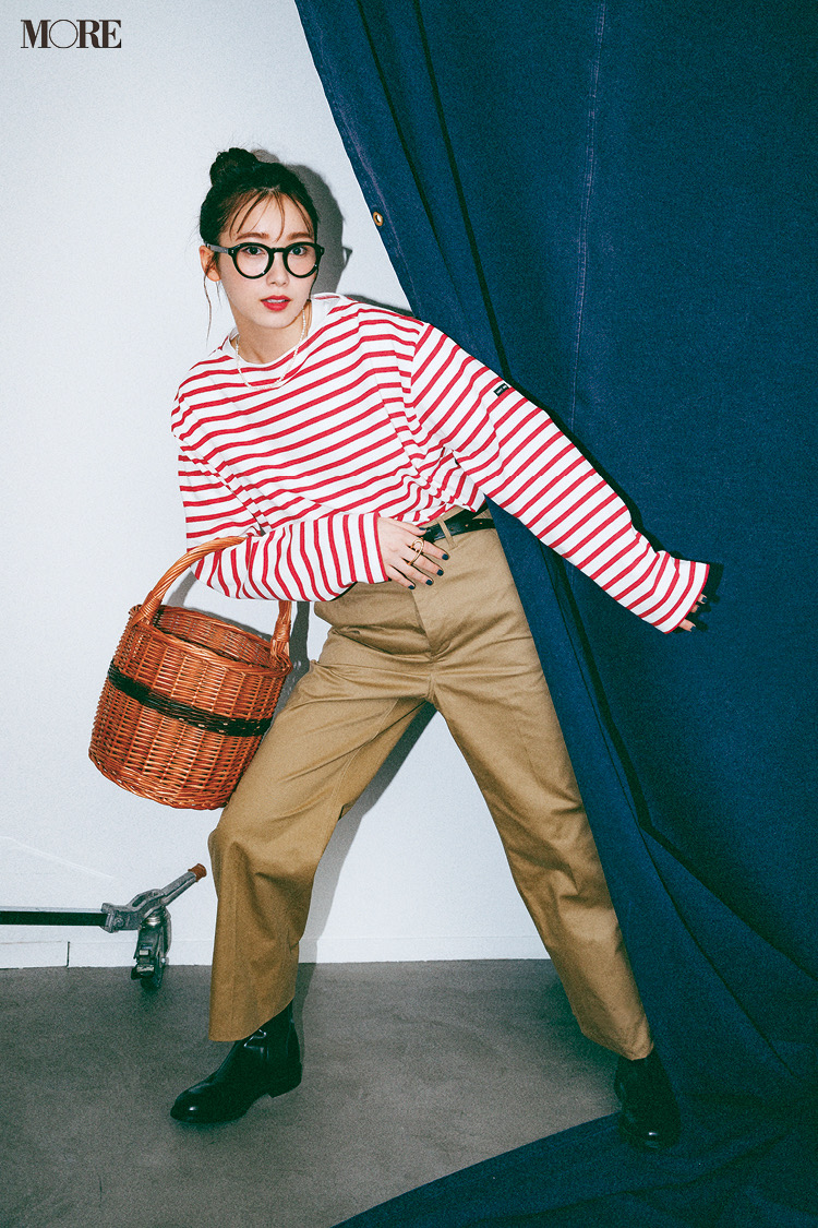 赤ボーダーのトップスとチノパンコーデに、メガネをかけてバスケットを持った飯豊まりえ