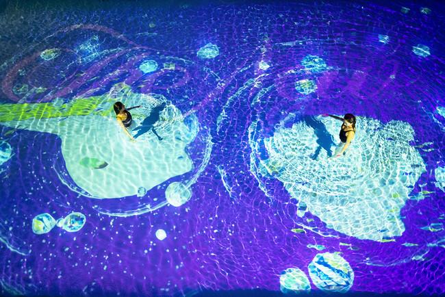 「NAKED NIGHT SAUNA HOTEL NEW OTANI -CITY RETREAT-」。夜の部でプールに入っている女性二人とアートの様子