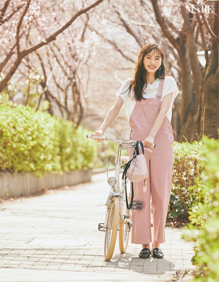 白T×ピンクのサロペットコーデで自転車を押す井桁弘恵