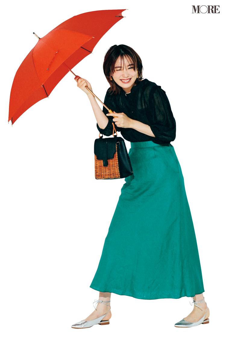黒ブラウス×グリーンのスカートコーデで傘をさした飯豊まりえ