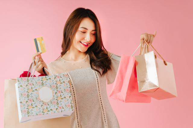 複数のショッピングバッグを手に持っている女性