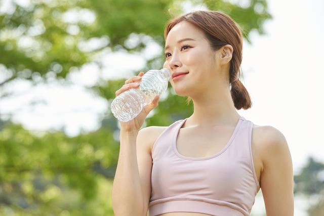スポーツブラを着用した女性が水を飲んでいる様子