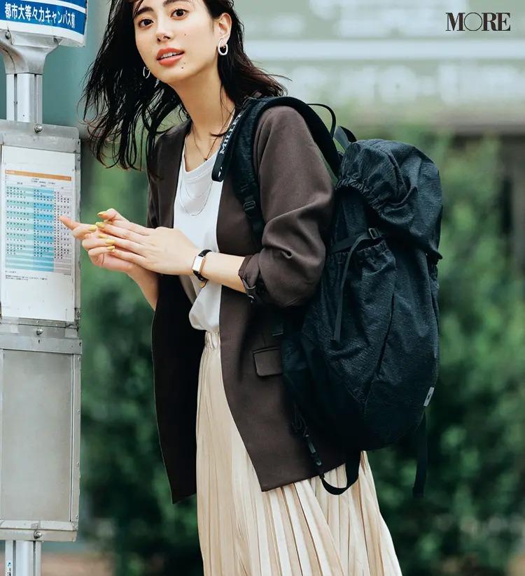 【通勤リュックコーデ】Tシャツ×プリーツスカート×ジャケットのコーデにリュックを背負った女性