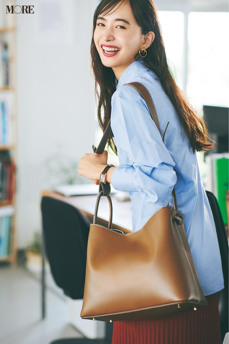 水色シャツ×リブニットスカートコーデで大きめのレザーバッグを持った井桁弘恵