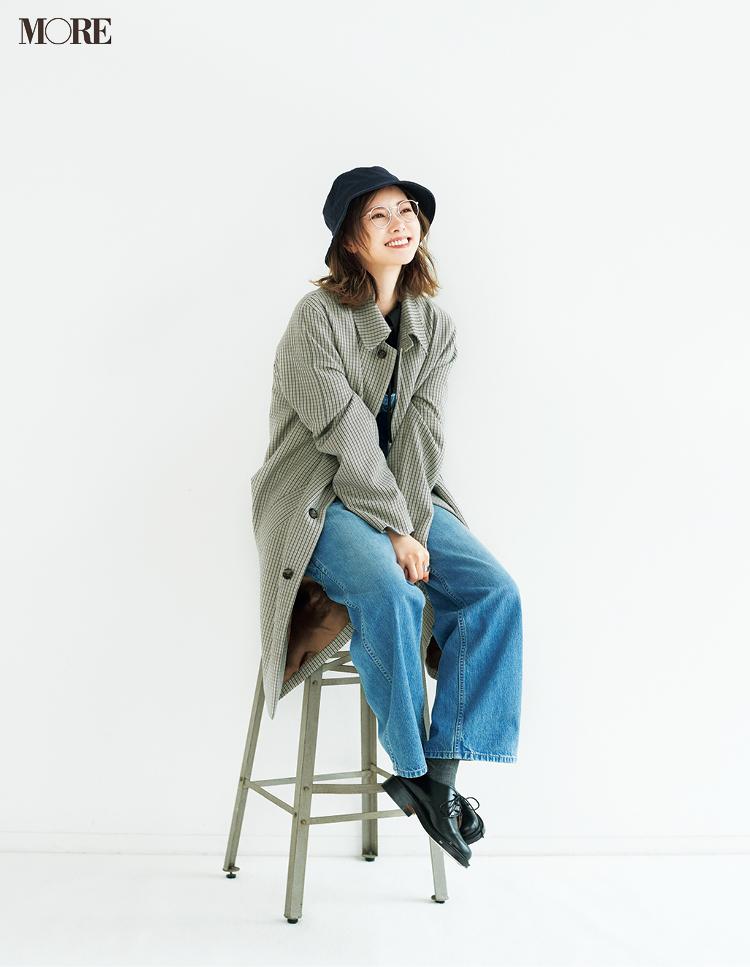 帽子と眼鏡とデニムパンツを身につけて椅子に座る白石麻衣