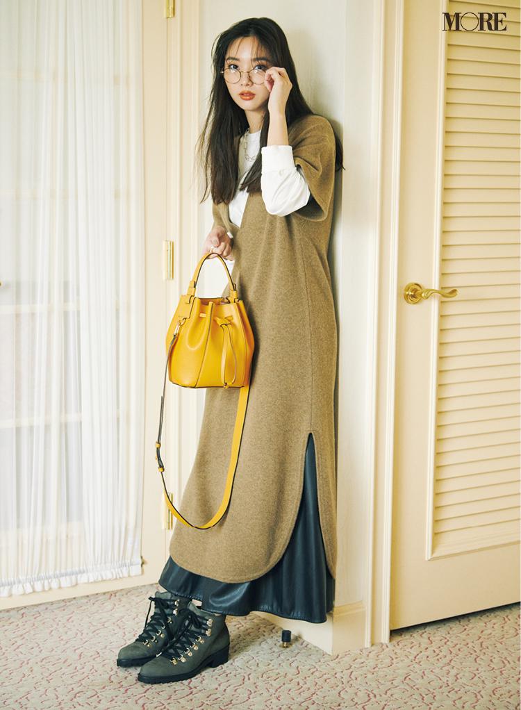 ニットワンピを着てメガネをかけ、フルラミアステラミニバケットバッグを持った新川優愛