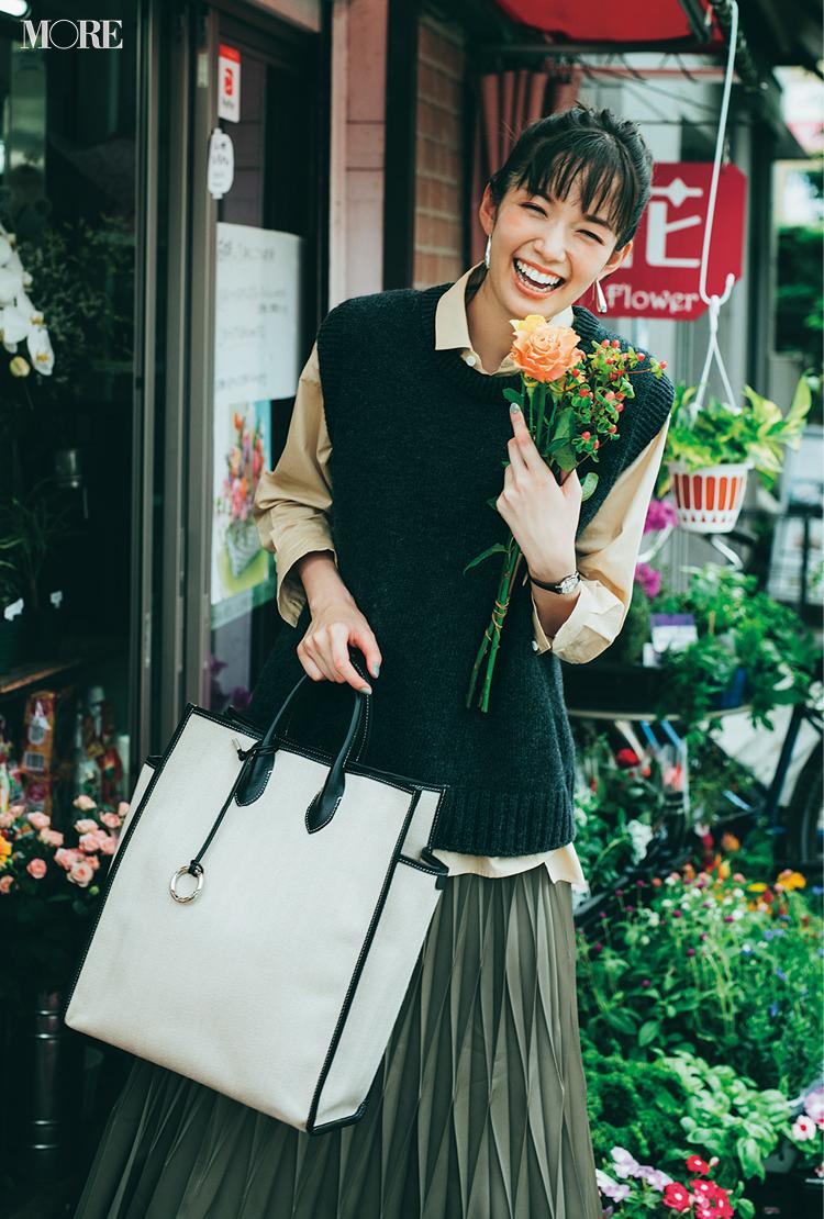 シャツにニットベストをレイヤードして花を持った佐藤栞里