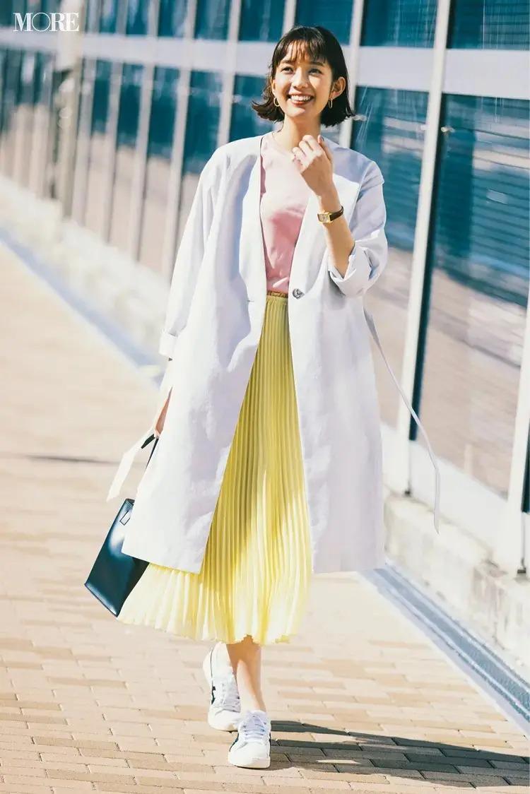 【春のスニーカーコーデ】白コート×ピンクのカットソー×イエローのプリーツスカート×白レザースニーカー