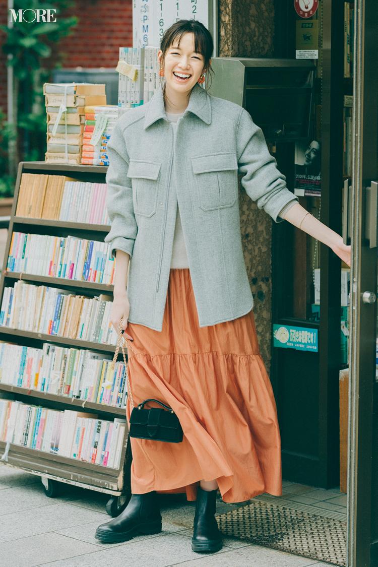 オレンジ色のスカートにごつめブーツの佐藤栞里