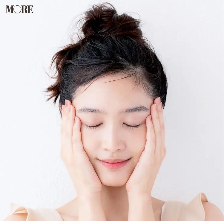 化粧水を両手にとって顔にハンドプレスしている女性