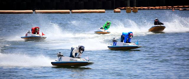 競艇場でボートレーサーがカーブを曲がっている様子