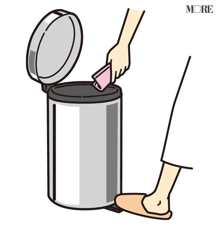 風水で開運を導く蓋付きのゴミ箱にゴミを捨てる人