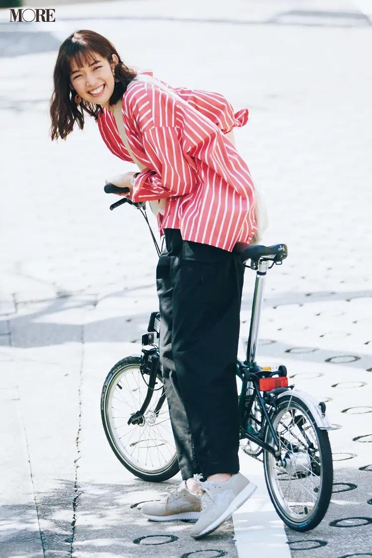 白Tシャツ×黒カーゴパンツコーデに赤いストライプシャツを羽織った佐藤栞里
