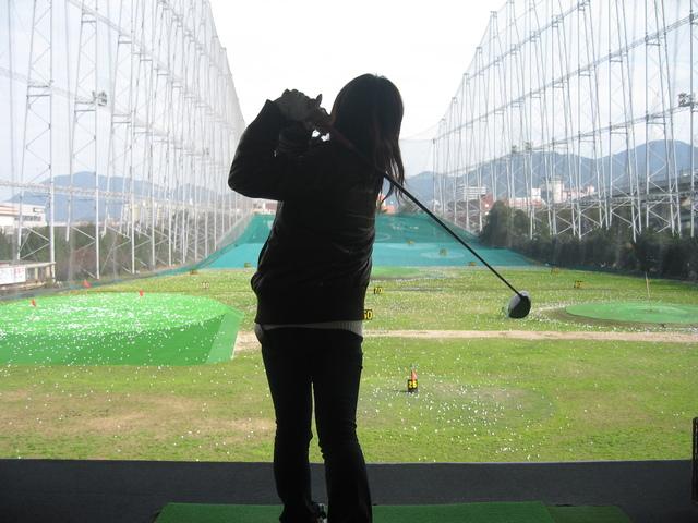 打ちっぱなしでゴルフクラブを振る女性の後ろ姿