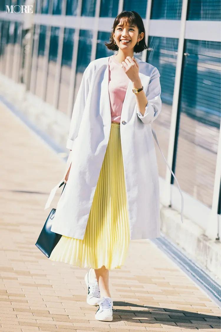 白コート×ピンクのカットソー×イエローのプリーツスカート×白スニーカーのきれいめコーデ