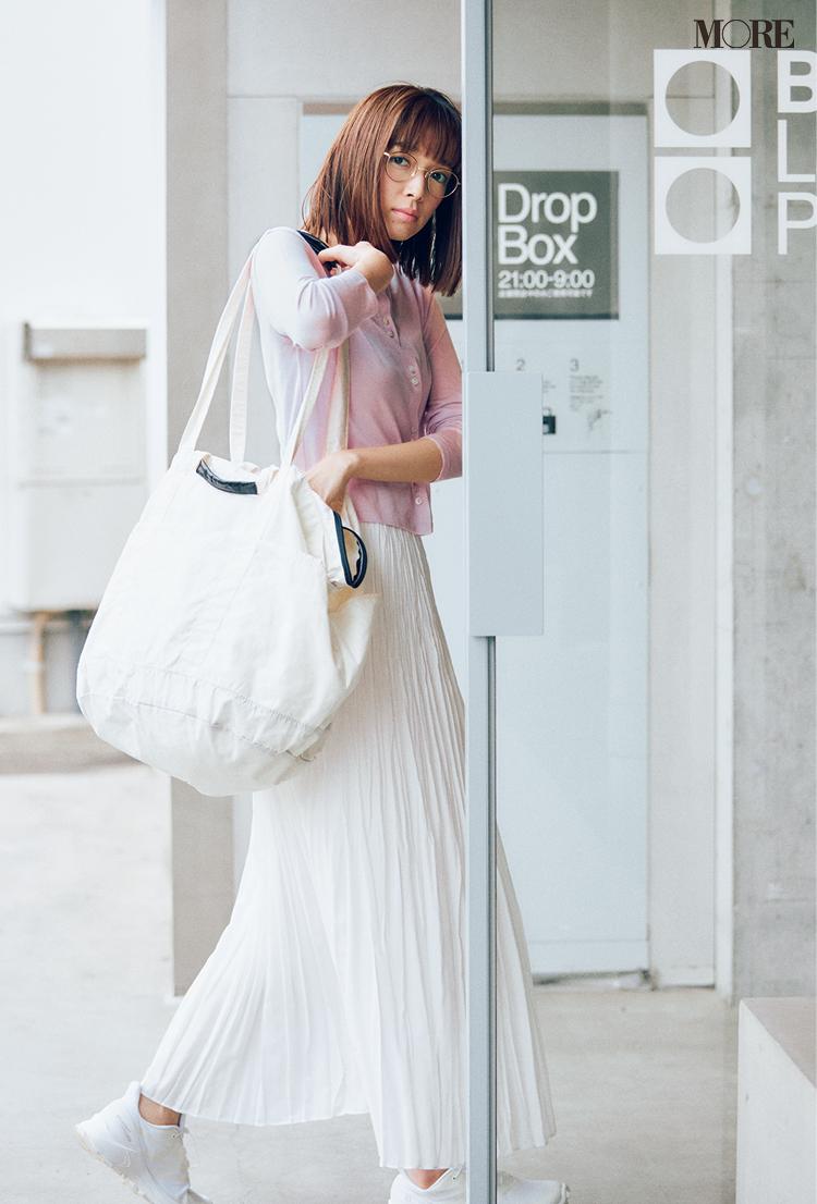 ピンクのカーディガン×白プリーツスカートコーデでメガネをかけた佐藤栞里
