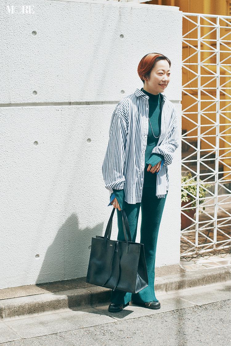 ニットセットアップにストライプシャツをはおった高野麻子さん