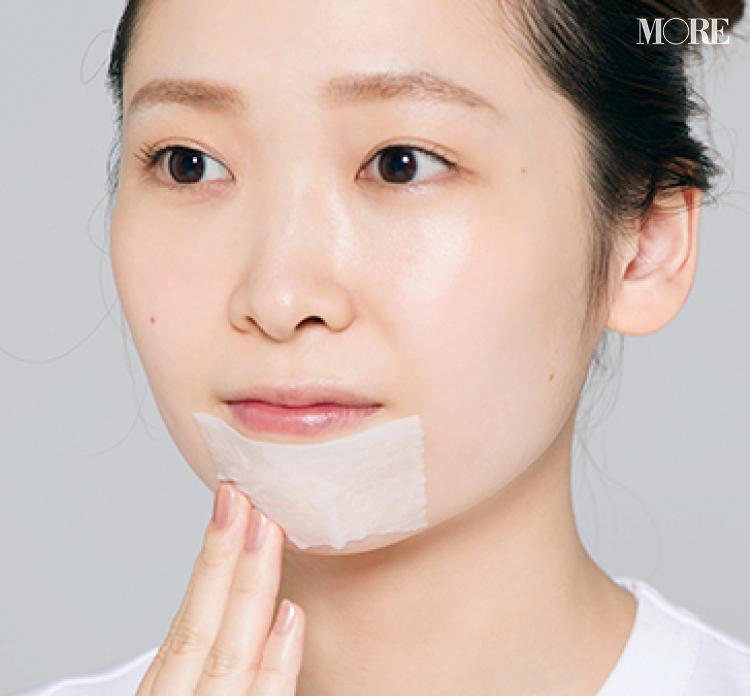 化粧水を染み込ませたコットンを顎につける女性