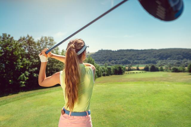 ゴルフ場でゴルフをするポニーテールの女性の後ろ姿