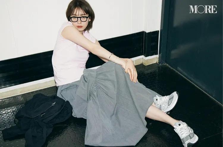 ピンクのコンパクトTシャツ×ロングスカートコーデでメガネをかけた飯豊まりえ