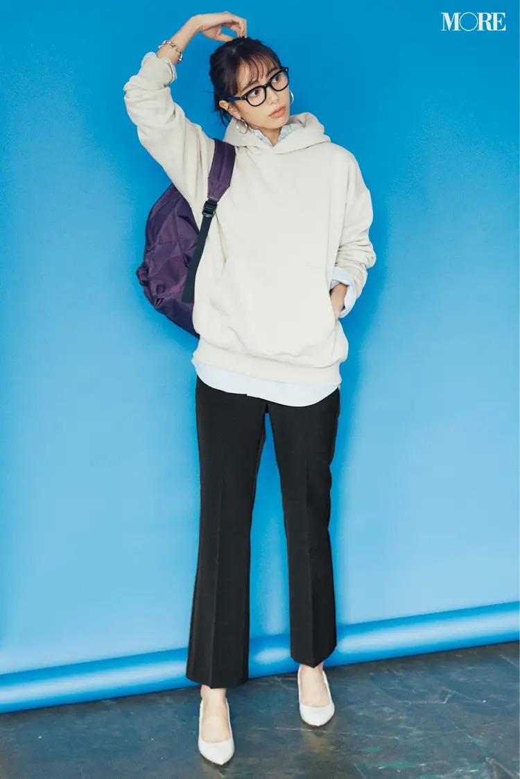 【通勤リュックコーデ】パーカ×シャツ×パンツのコーデにリュックを背負った女性