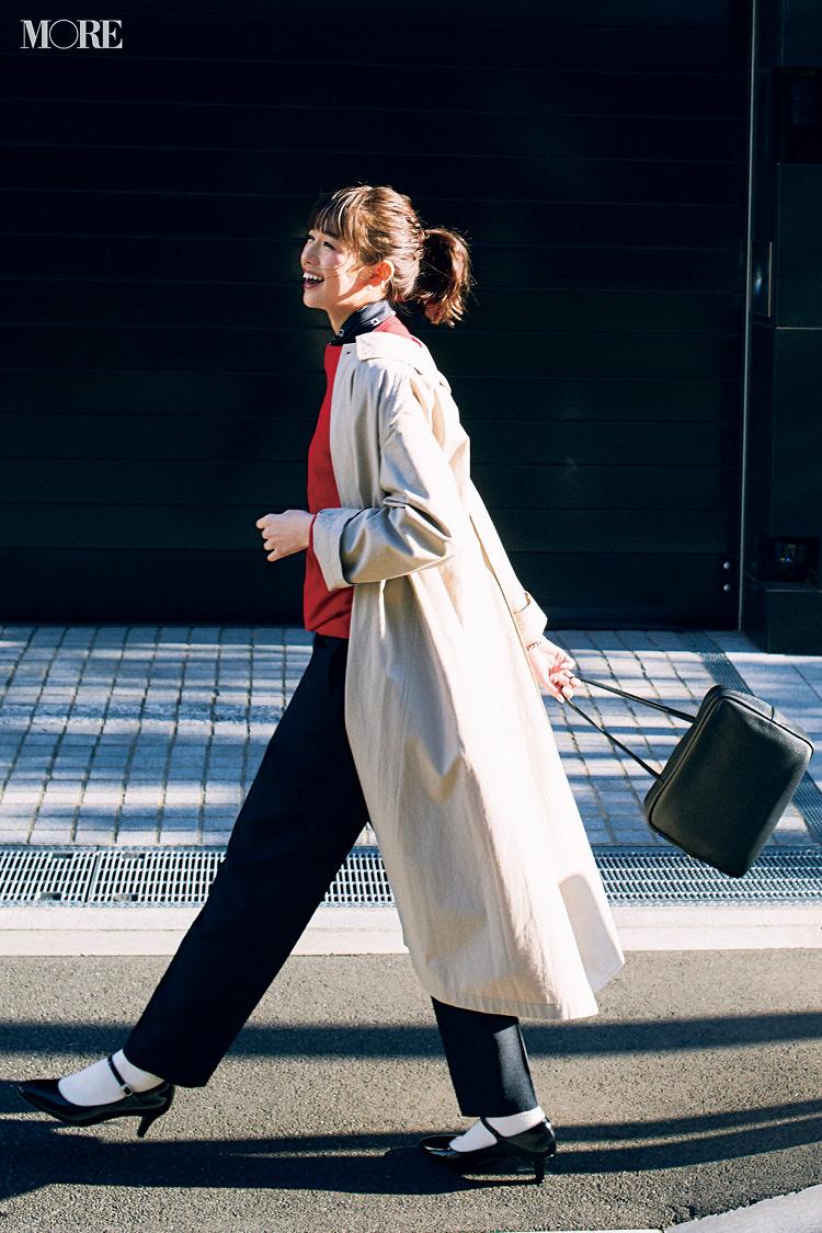 赤トップスと黒パンツにベージュのステンカラーコートをはおった佐藤栞里