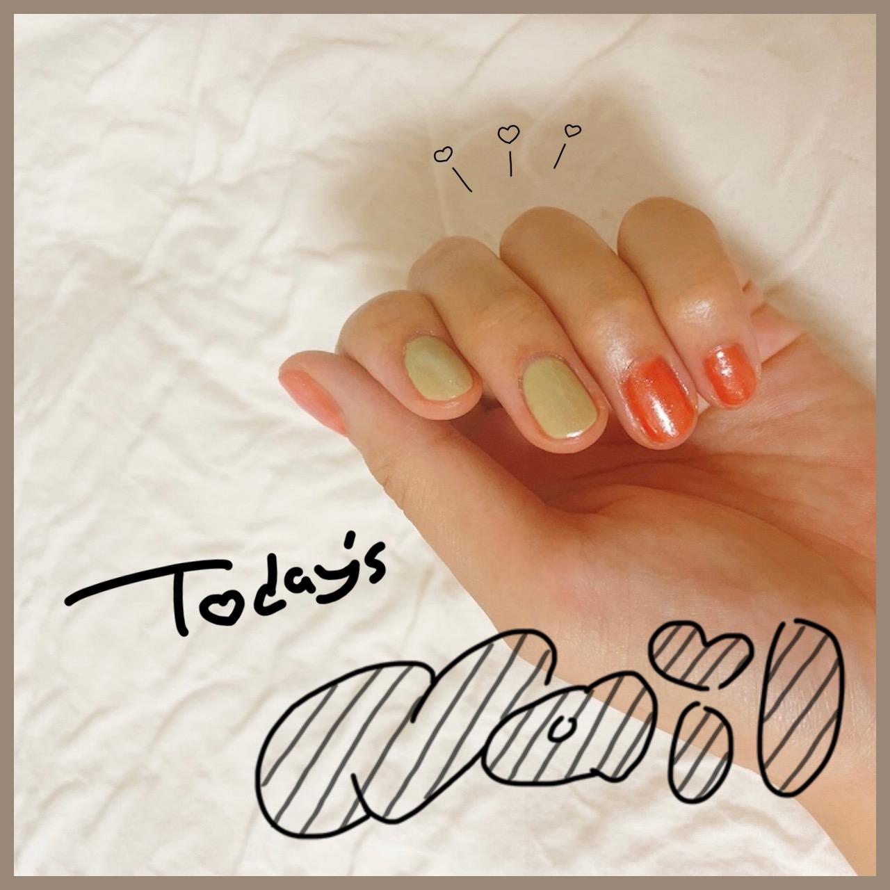 ジェルネイルをした左手の写真。爪がよく見えるように軽く握っている。人差し指と中指はピスタチオグリーン、その他の指はオレンジ。すべての指に白っぽいラメがのっている