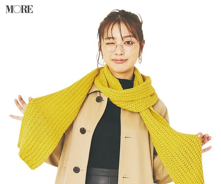 ケーブル編みマフラーをゆるく巻く女性