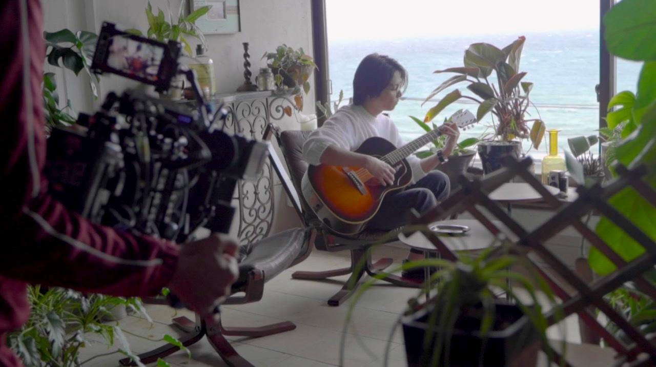 JINS&SUNのWEB CMのメイキングで、ギターを弾く山下智久