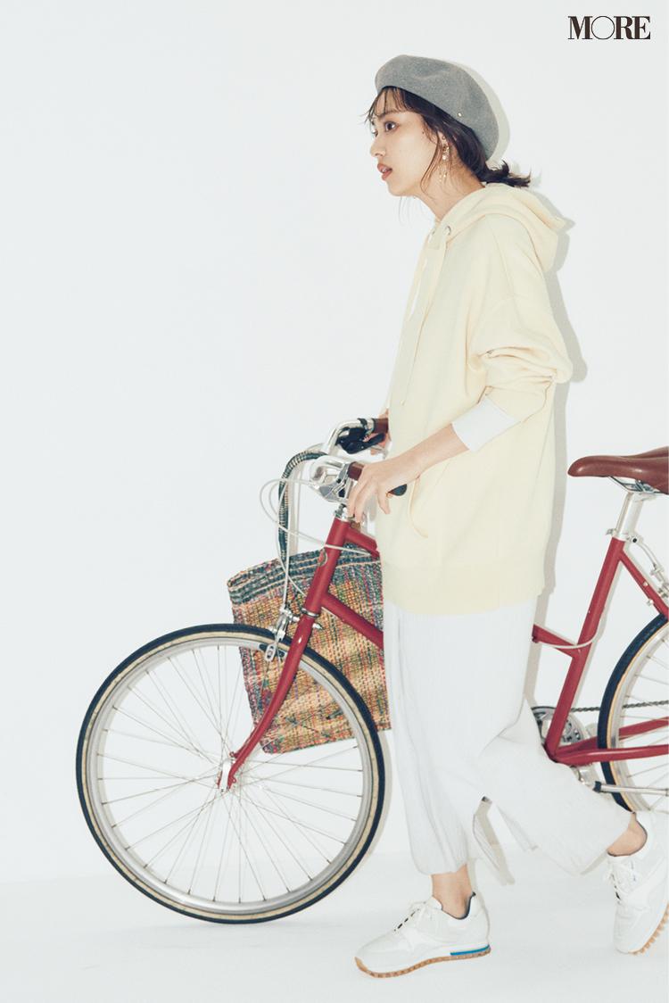 ロングカーディガンにフーディを重ねたコーデで自転車を押す内田理央
