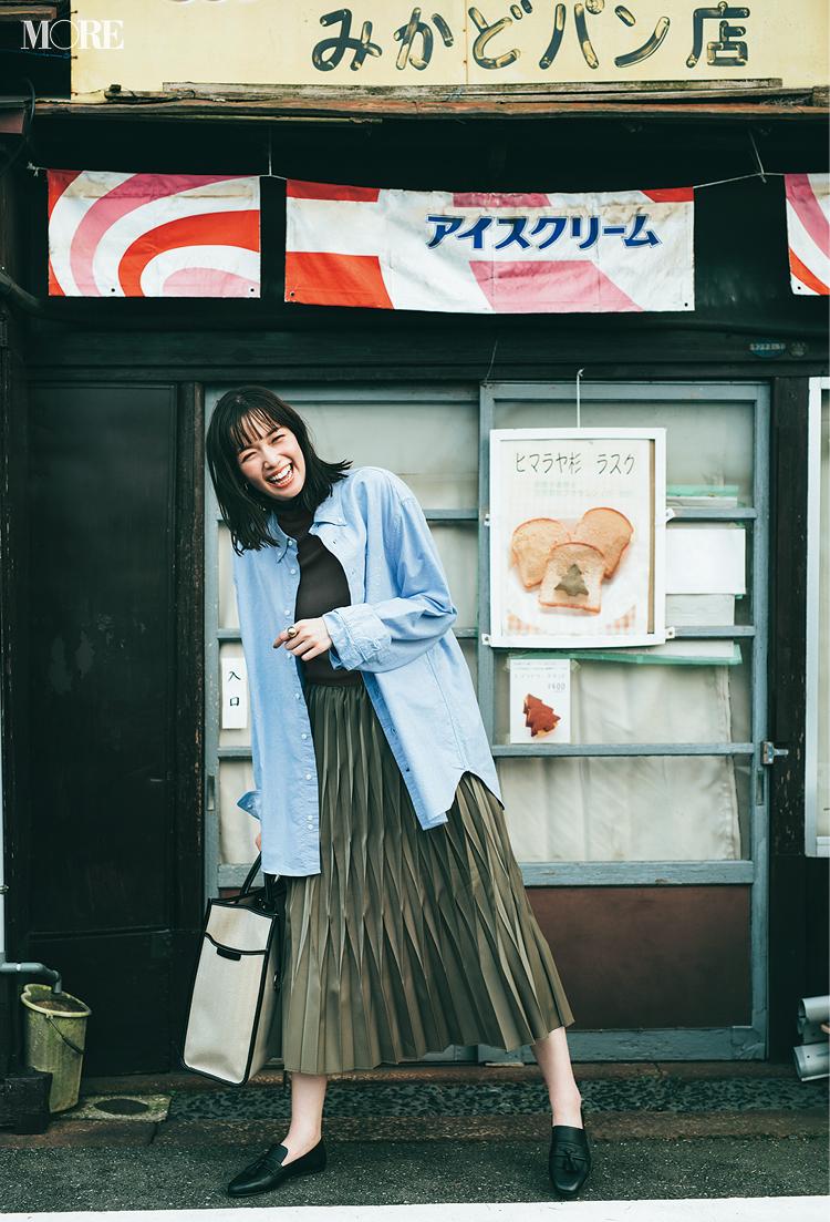 タートルネックニットにシャツをはおってプリーツスカートをはいた佐藤栞里