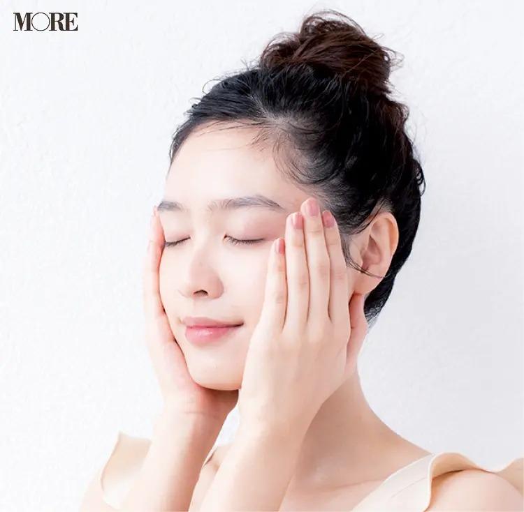 両手で顔をおさえるように乳液をつける女性