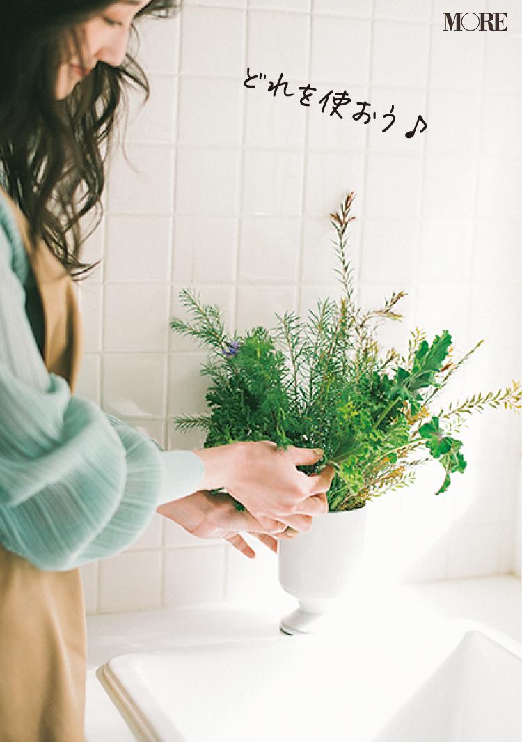 キッチンに飾ったハーブを摘む女性