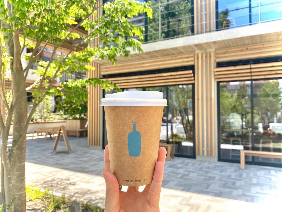 「ブルーボトルコーヒー 渋谷カフェ」を背景に、コーヒーカップを片手に持っている写真