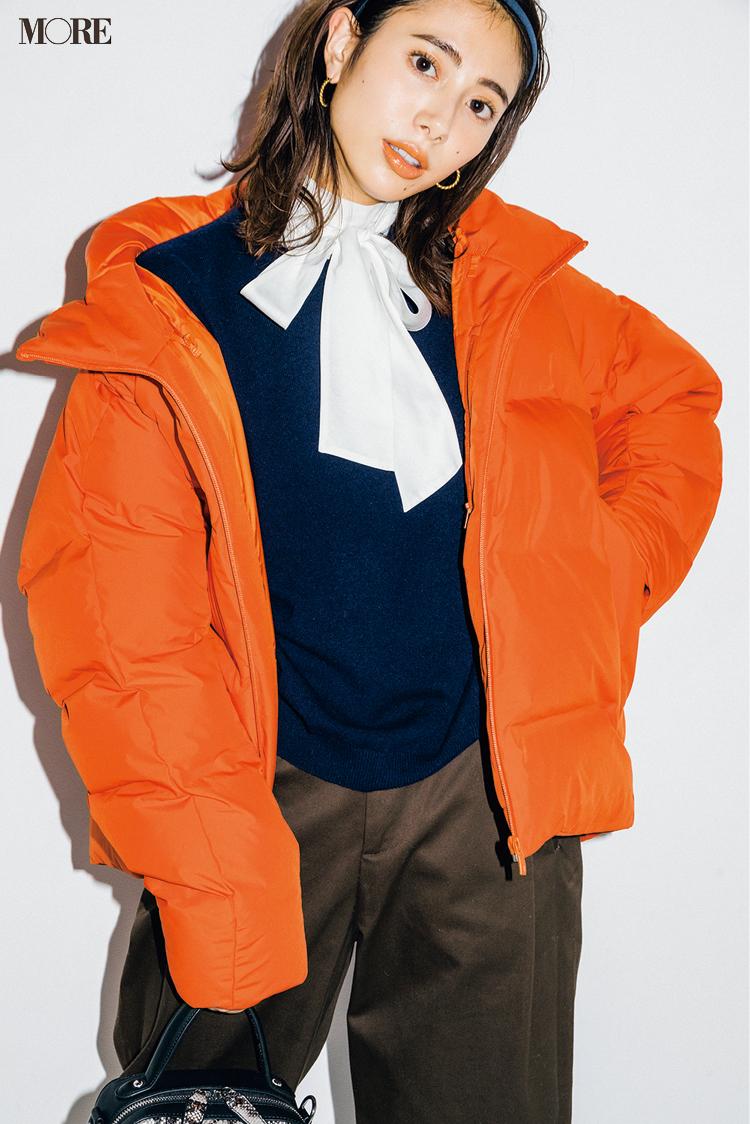 ユニクロのオレンジ色のダウンを着た土屋巴瑞季