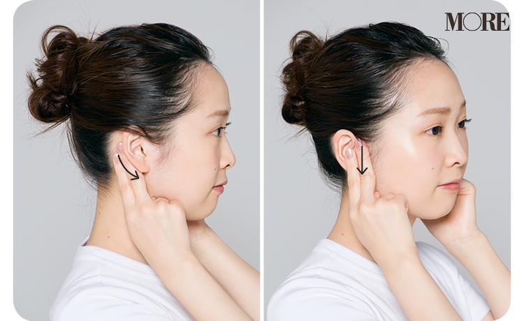 指2本で耳の前後を揉む女性