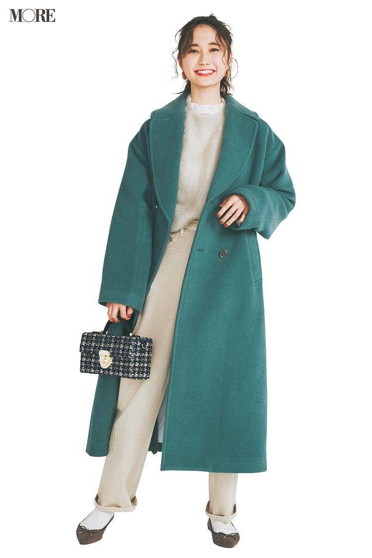 オフホワイトのワントーンにグリーンのコートをはおる