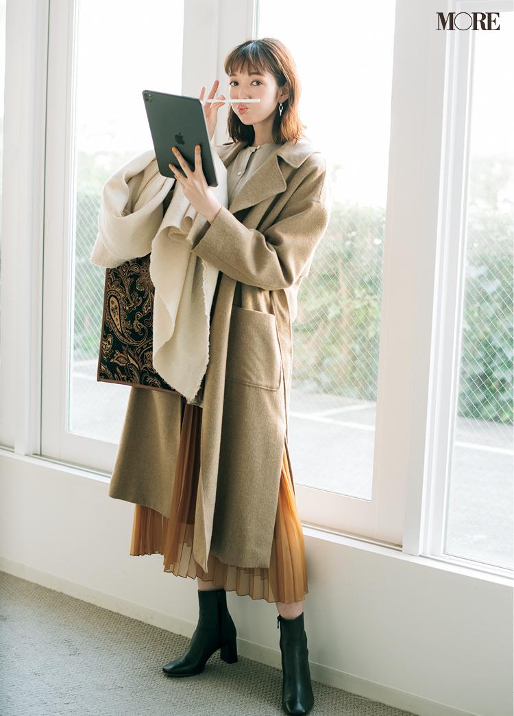 ベージュのコートをはおった佐藤栞里