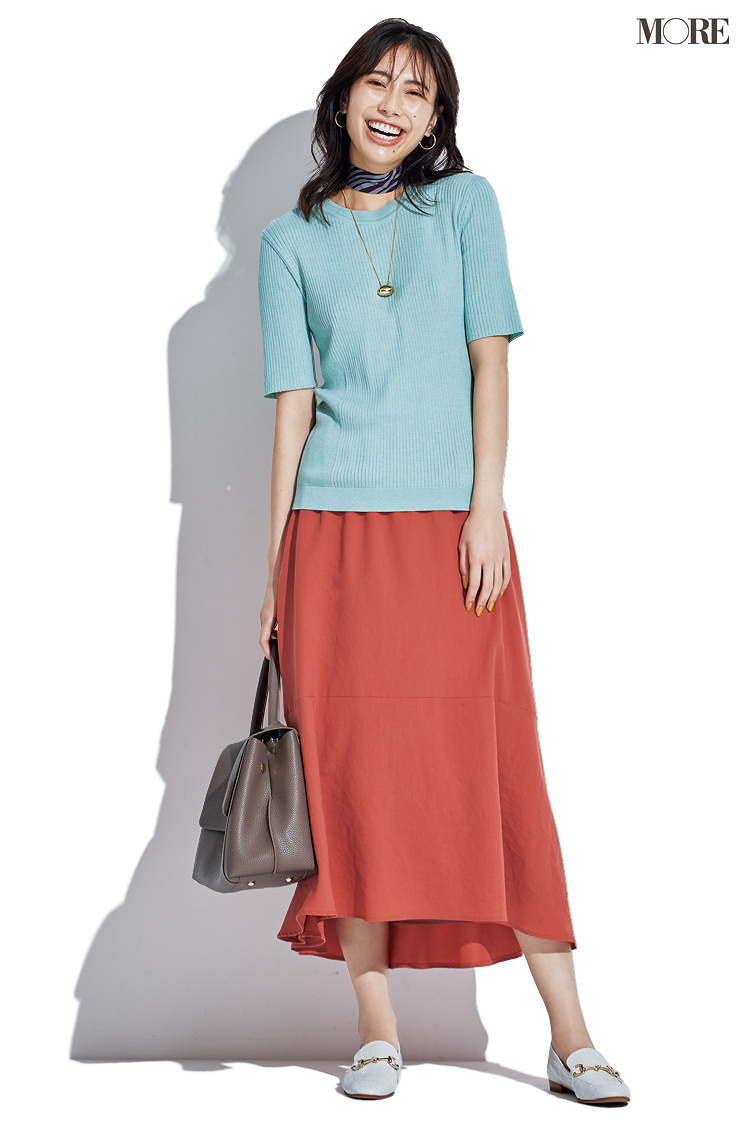 ミントグリーンのトップスと赤いスカート