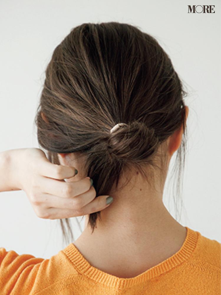 梅雨の低めおだんごヘアアレンジで結び目を調節する女性