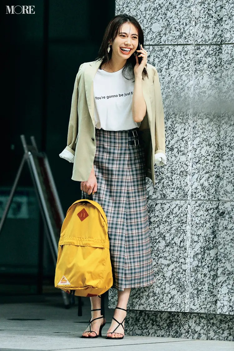 【通勤リュックコーデ】Tシャツ×チェック柄スカート×ジャケットのコーデにリュックを持った女性
