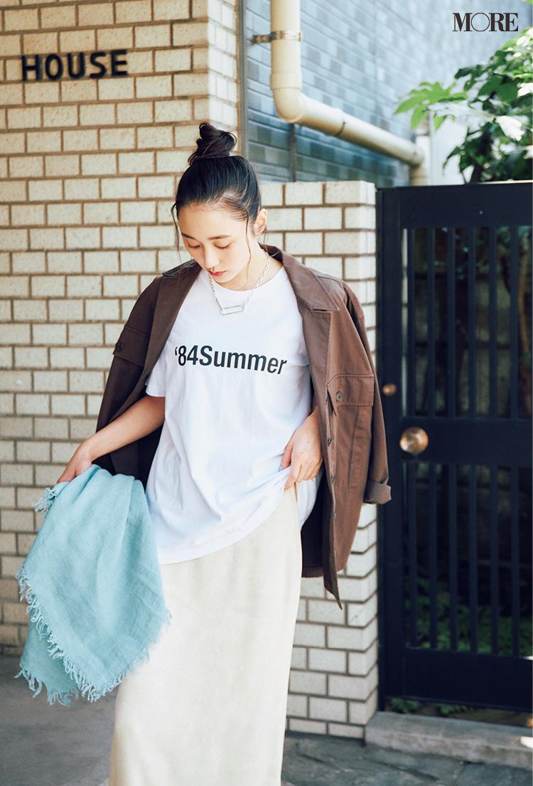 白いロゴTシャツをワントーンのスカートとブラウンジャケットで着回す