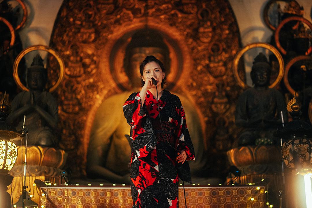 仏像の前で歌うyui