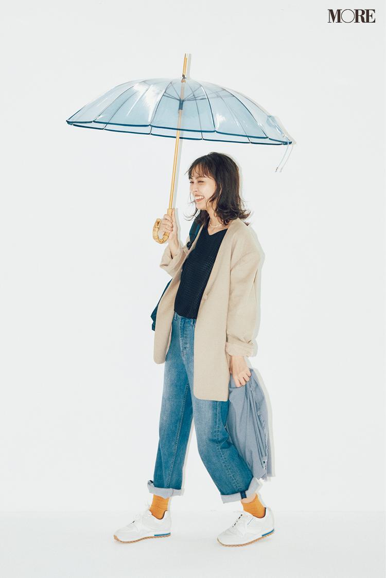 ジャケットとデニムコーデで傘をさしている内田理央
