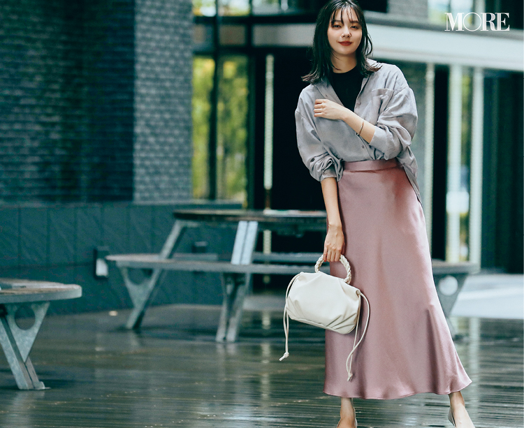 くすみピンクのナローフレアスカートをはいた新川優愛
